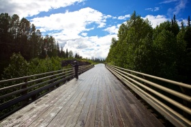 """One of the many """"slick"""" wooden bridges crossings along the Cassiar Hwy."""
